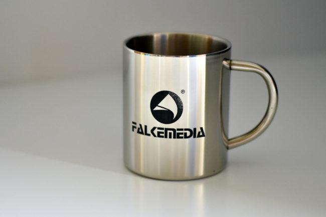 Ein Kaffeebecher aus Metall mit eingraviertem Logo von FALKEmedia.
