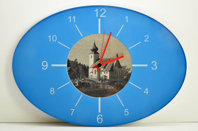 Blaue Wanduhr mit eingraviertem Kirchenmotiv