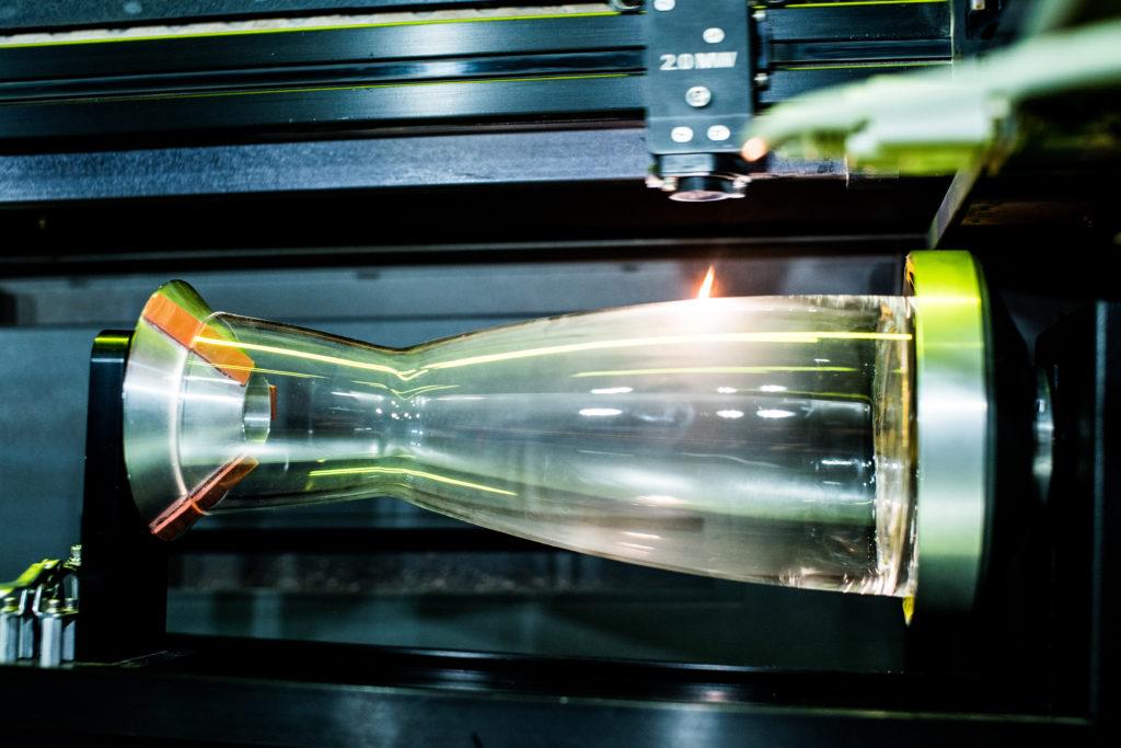 Eine Wasserkaraffe wird gerade mittels Lasergravur mit einem Logo versehen
