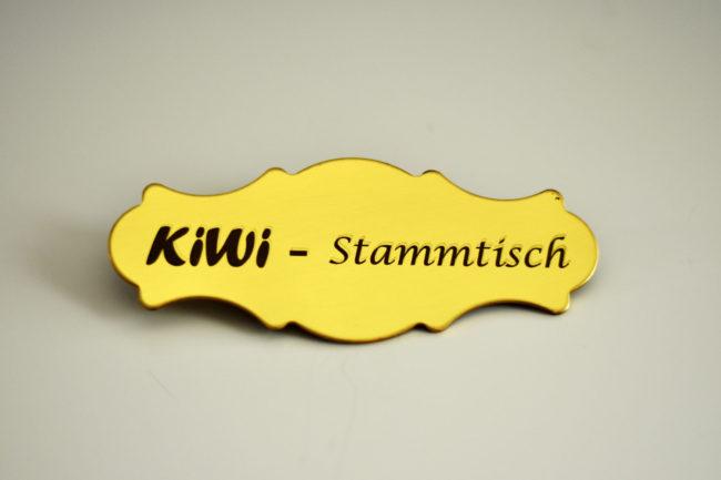 Gelber Anstecker mit dem Schriftzug Kiwi - Stammtisch
