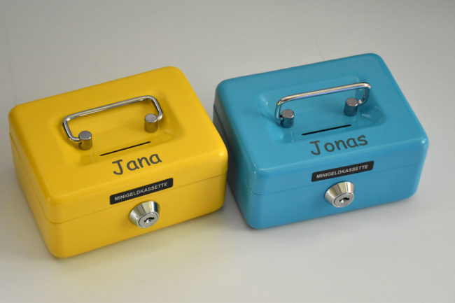 Zwei kleine Geldkassetten in blau und gelb mit den Namen Jana und Jonas graviert